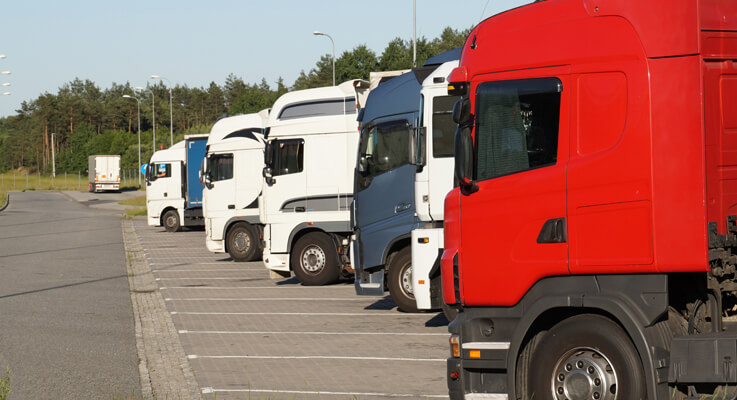 Multiple colored semi trucks lined up at a truck stop