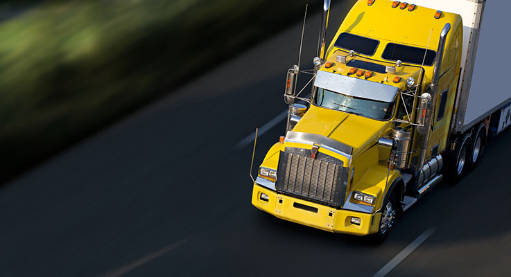 Yellow semi truck driving on the freeway