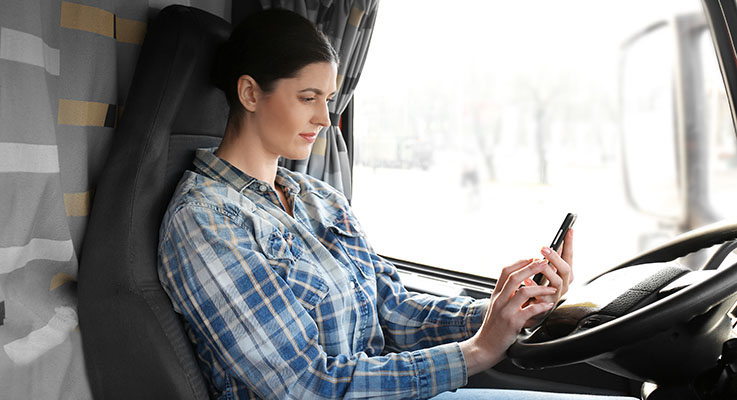 Truck driver using a trucker app on her smartphone