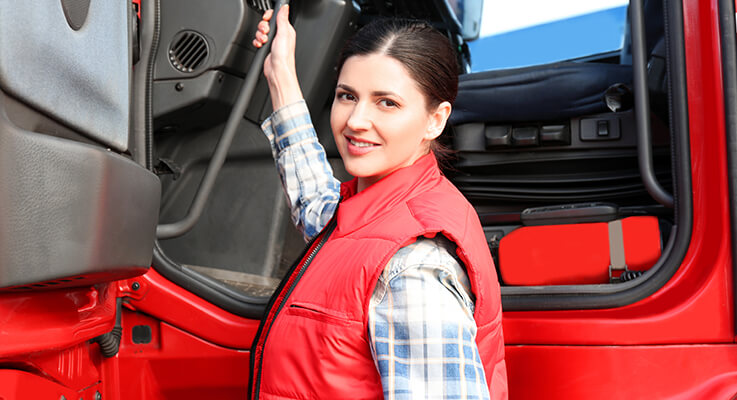 Woman in red vest climbing into red semi truck