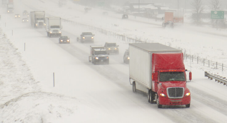 Red semi truck driving on freeway in a blizzard